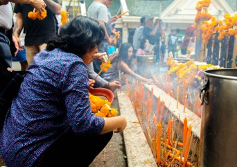 Lighting incense at the site of the recent Bangkok bombings.