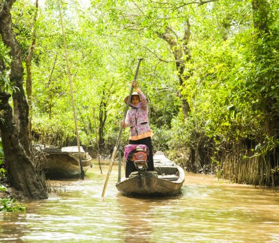 A resident from the one of the river villages, paddling past to pick up her shopping from the floating market.