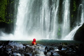 A hooded lady stairs down the waterfall of Gunung Rinjani