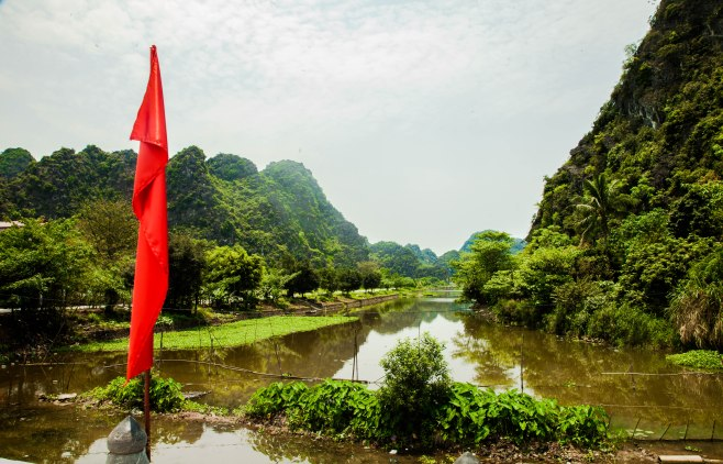 The red flag stands out against the green hills of Ninh Binh.